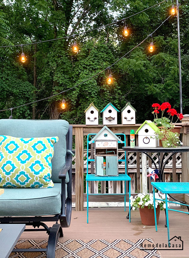 deck decorated for Summer with string lights and bird houses
