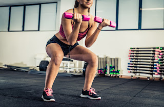 Woman squatting with dumbbells