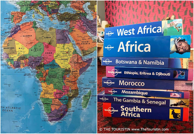 The map of Africa next to a stack of African travel guide books in front of a magenta coloured wallpaper featuring black cats.