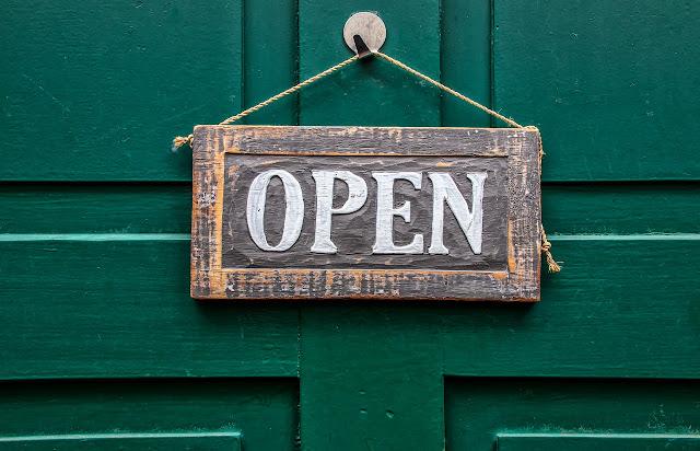 Ovessa roikkuva puinen kyltti, jossa lukee Open - Auki.
