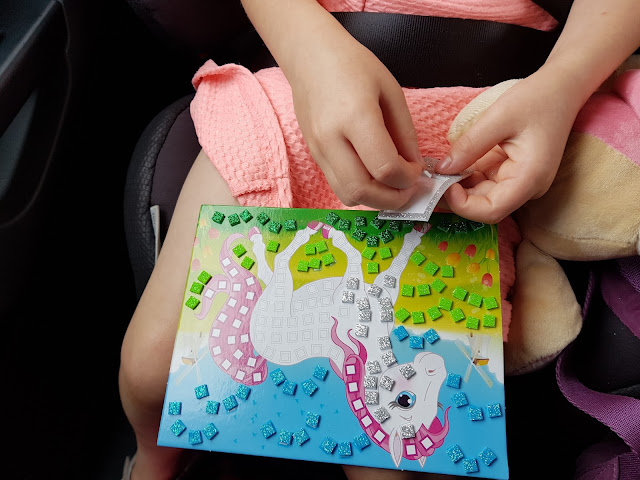 A close up of M taking the foam squares off and sticking them on the Pony Craft Time mosaic