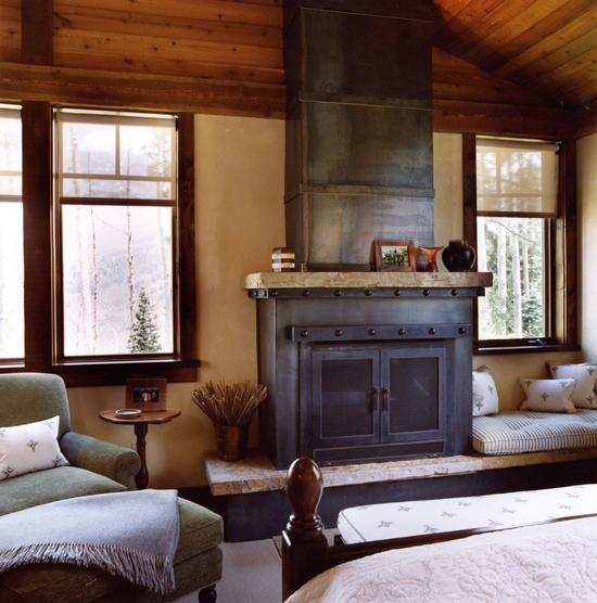 Cozy bedroom with iron fireplace by Elizabeth Dinkel Design