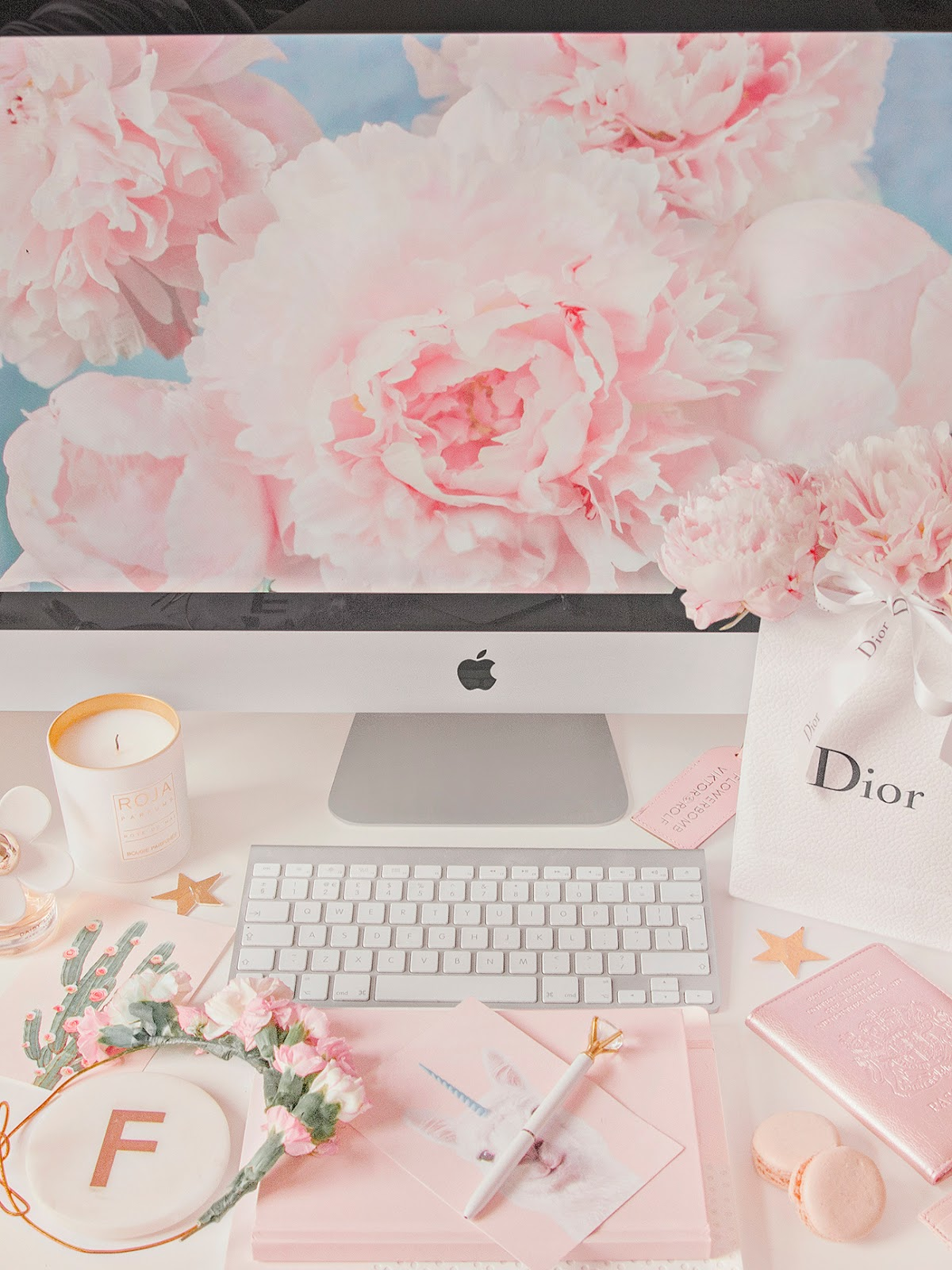 Photo of a desk with an iMac showing a wallpaper of peonies