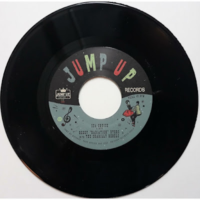 The single's paper sleeve features the band, song title, and label imprint (Jump Up), as well as an illustration of a couple dancing.