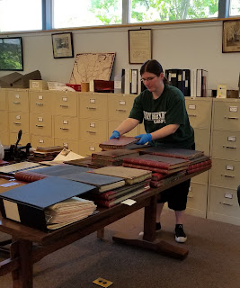 Photo of Marietta arranging large books on a table in the SCHS library.