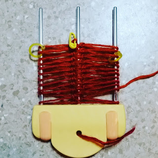 A clover hairpin loom on the widest setting with a central pin. There are approximately 10 loops of red yarn on the loom with yellow stitch markers on each side and on the working loop in the centre. the hand held loom consists of a yellow base with three metal prongs pointing upwards. The loose end of yarn from the start of the ball is threaded through a hole in the loom's base.