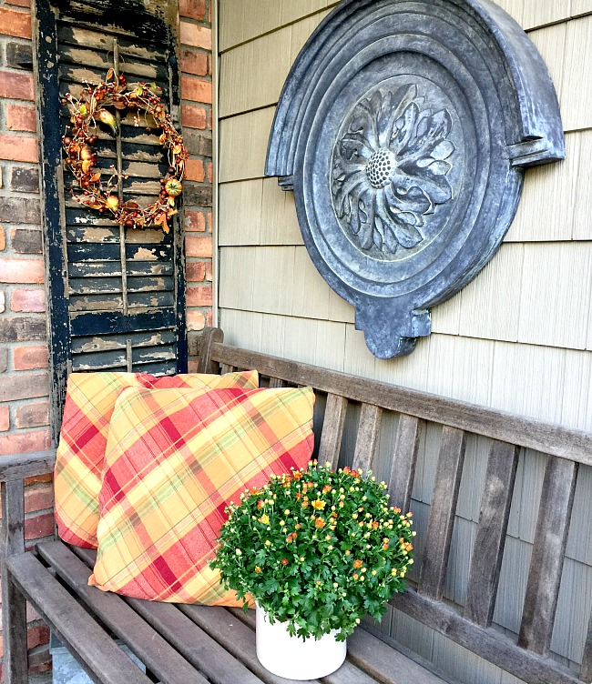 Outdoor bench with shutter, flowers and pillows