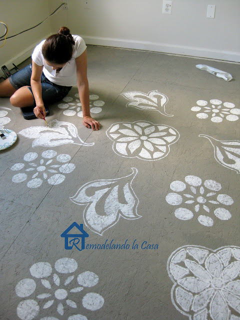 woman painting floral designs on floor, gray, white, brush, paint