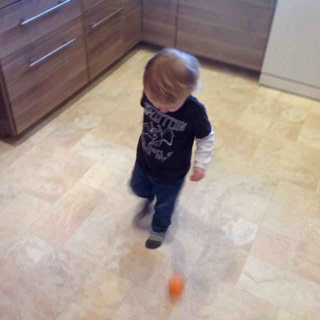 toddler palying football in the kitchen