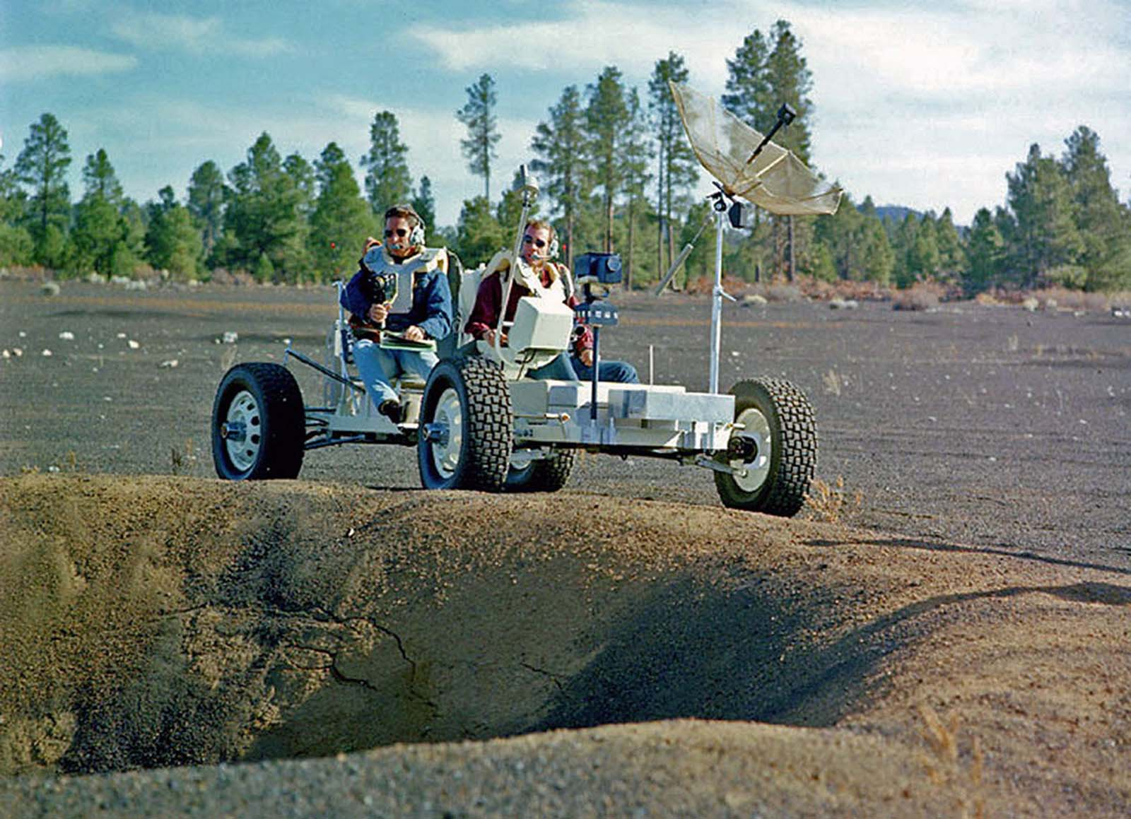 The astronauts Jim Irwin and Dave Scott pilot Grover near the rim of a large crater in the Cinder Lake Crater Field.