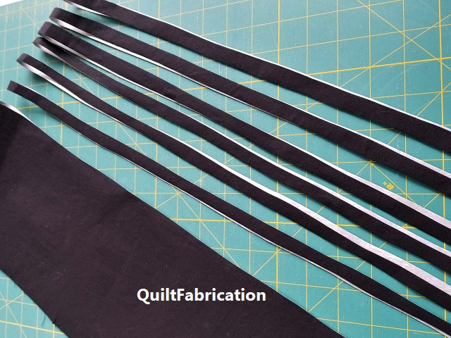 freehand cutting fused black into 1/2 inch WOF stripes