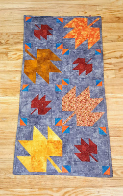 yellow and red leaves on a grey background for a table runner