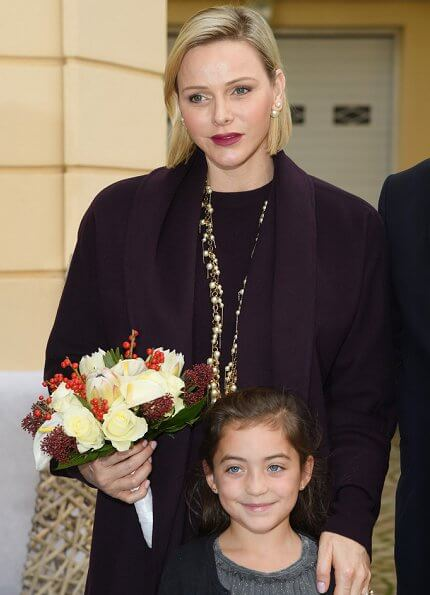 Princess Charlene wore a wool cashmere brown coat and brown long sleeve wool midi dress by Louis Vuitton