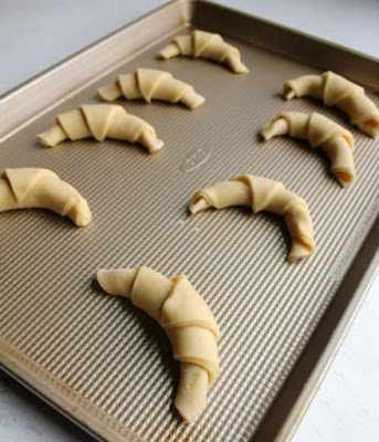 crescent roll dough rolled into horns and ready to proof