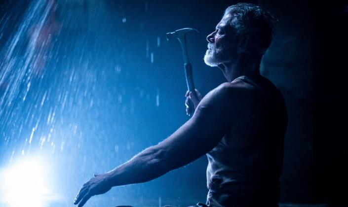 Imagem: fundo escuro com apenas uma iluminação de uma lanterna, em que vemos água escorrendo do alto e um homem velho com barba curta e uma camisa branca erguendo um martelo no alto.