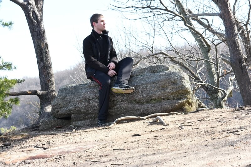 Автор сидит на камне, на краю обрыва, и смотрит в сторону, как  бы о чем-то размышляя.
