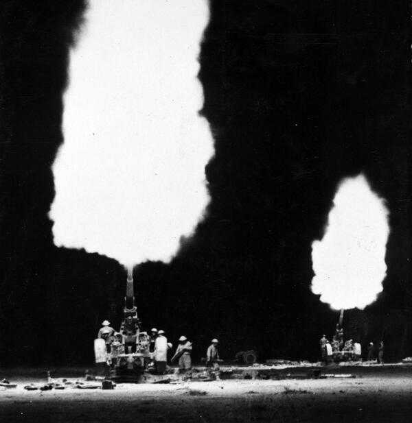 British gunners firing their 114-mm anti-aircraft guns against German positions, during the night near Tobruk, Libya , January 1941.