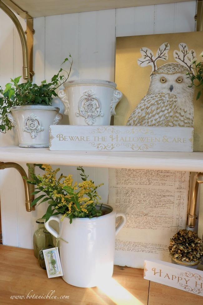 White ceramic urns with raised French style medallions add French Country style to open shelves