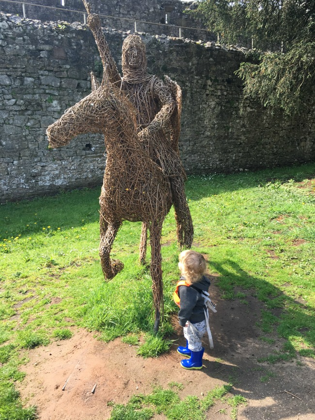 wicker horse and knight with toddler looking up