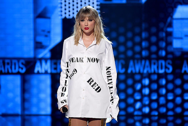 Taylor Swift 2019 AMA performance wearing white shirt with record labels