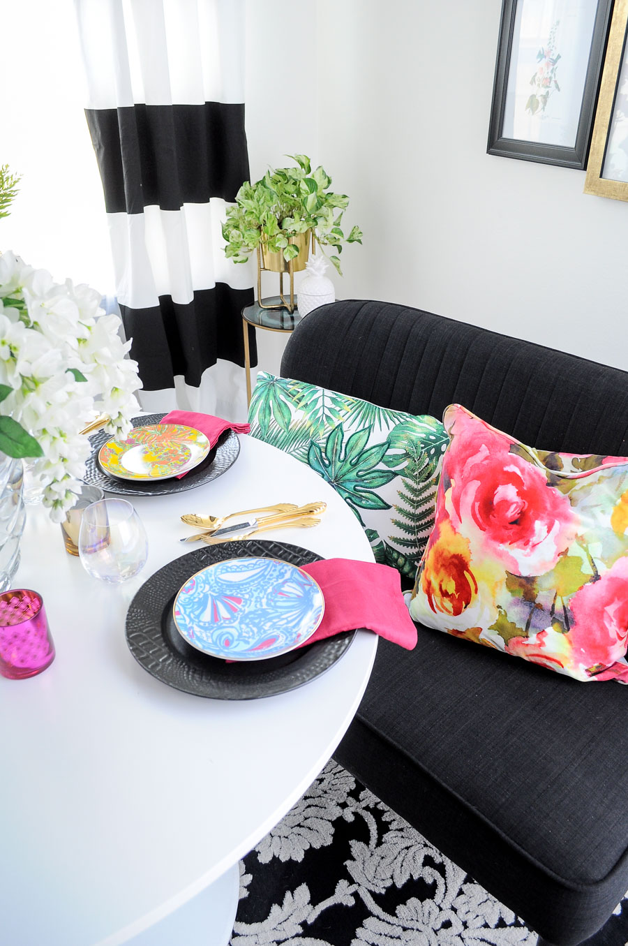 A colorful, floral and eclectic small dining space featuring gorgeous black and white striped curtains.