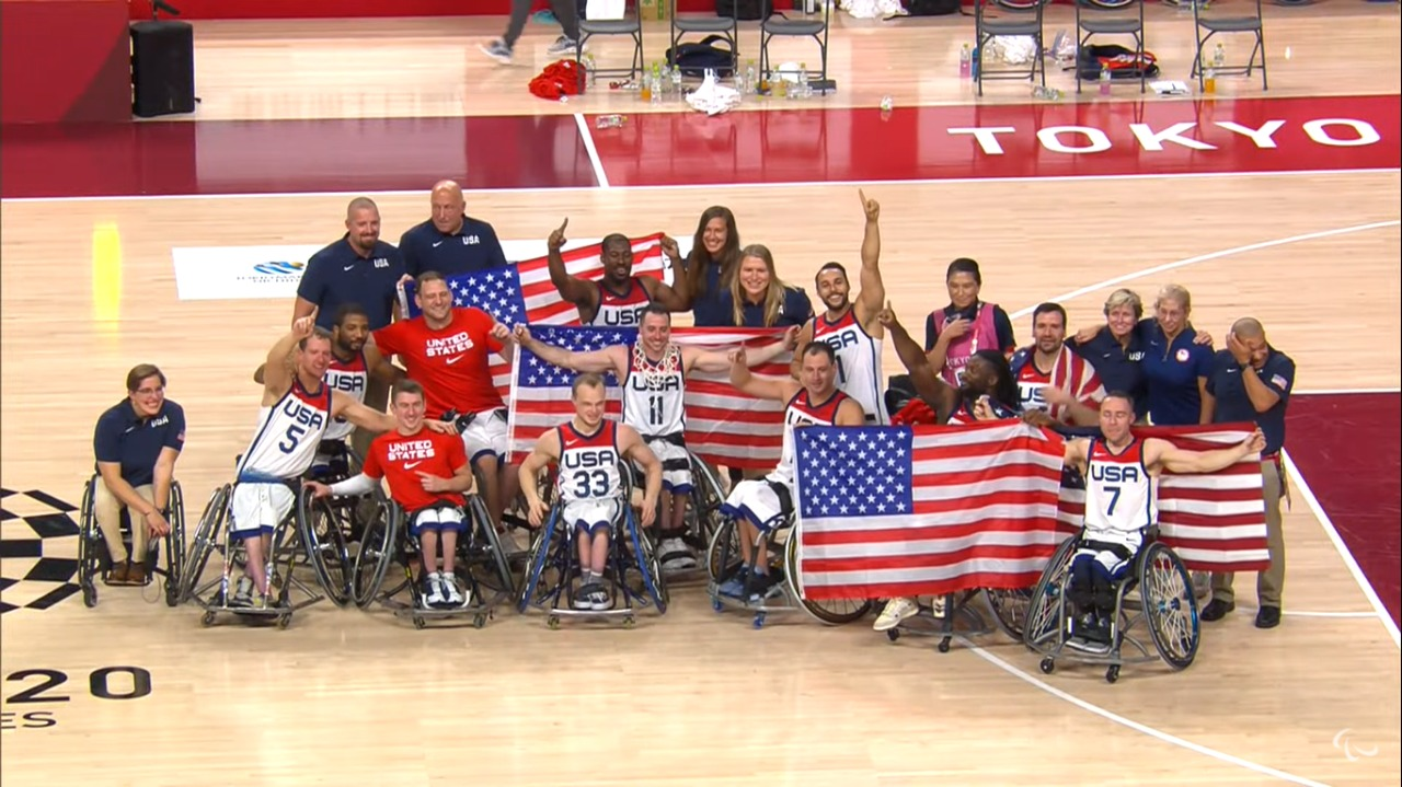 Seleção dos Estados Unidos e comissão técnica posa para foto, segurando bandeiras do país