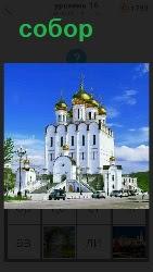 стоит высокий собор белого цвета с позолоченными куполами