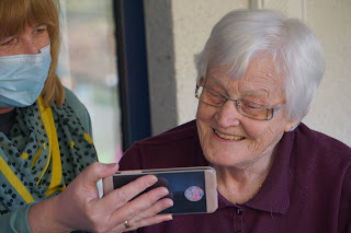 masked staff member helping elderly woman with video chat