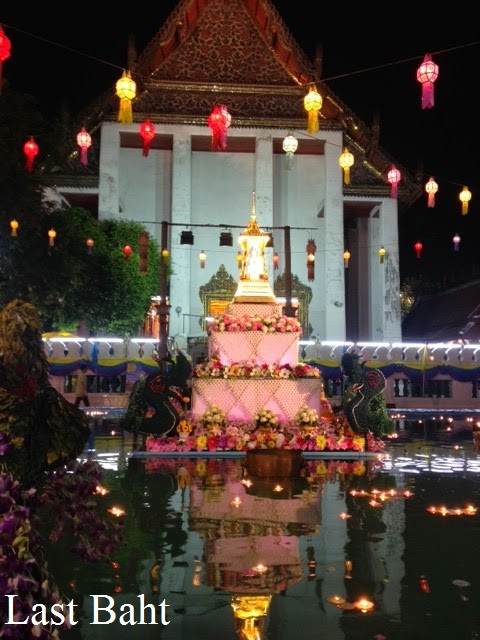 candles float on a pond outside a temple on Loi Krathong night in Bangkok