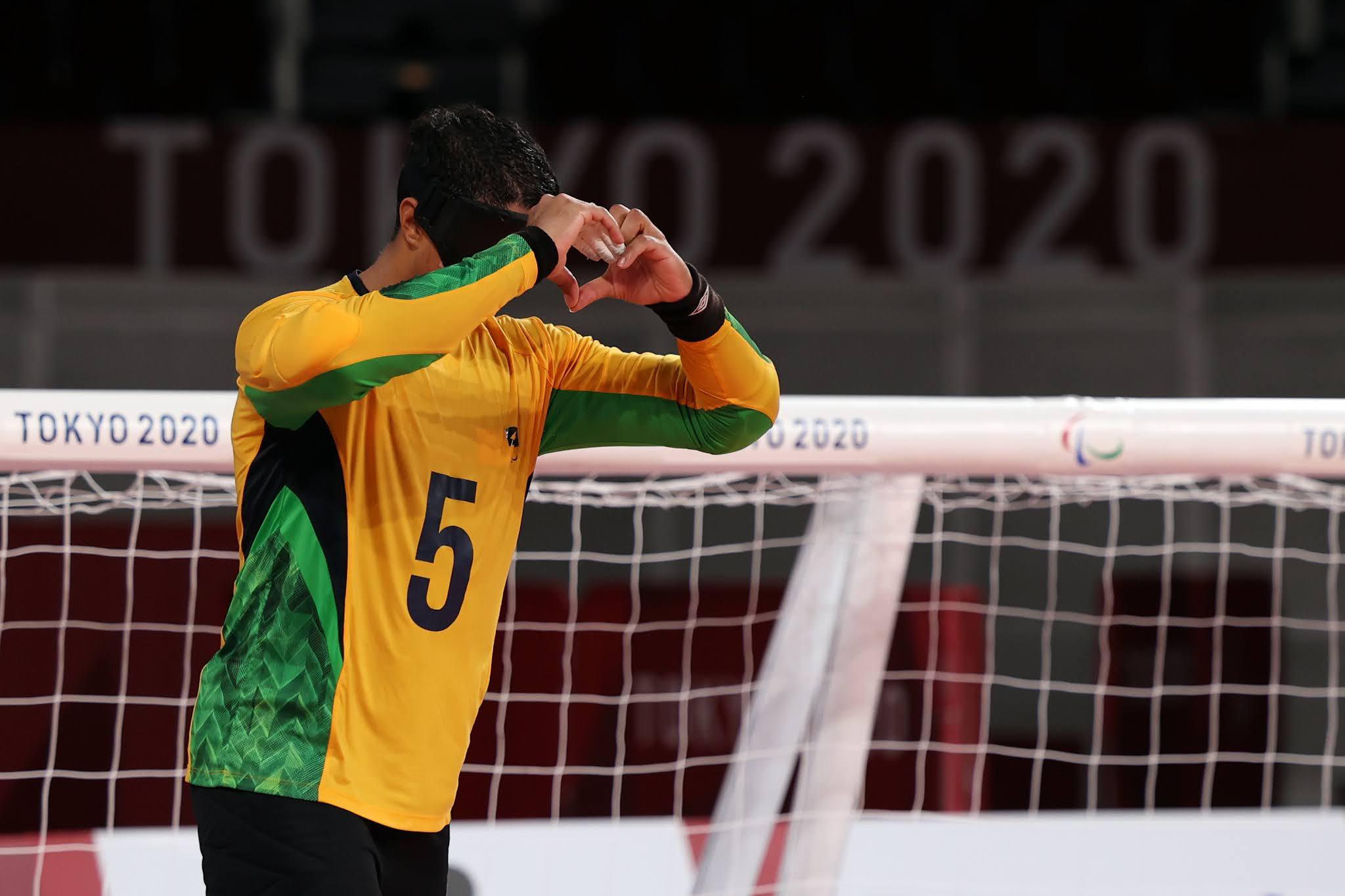 O atleta Parazinho de amarelo e com o número cinco em sua camisa faz um gesto de coração para a frente com as mãos