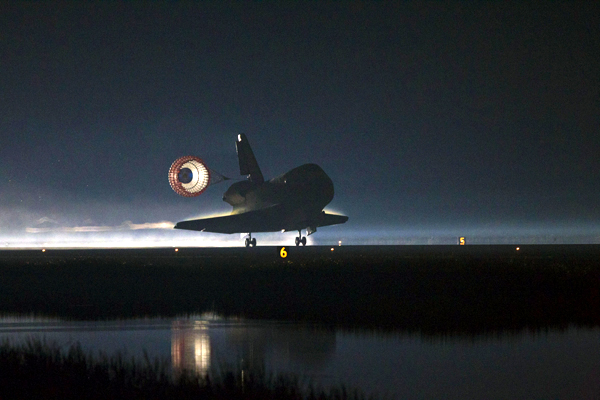 The orbiter Atlantis deploys her drogue chute as she touches down on the Shuttle Landing Facility's Runway 15 at NASA's Kennedy Space Center in Florida...completing mission STS-135 on July 21, 2011.