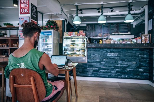 Seorang pria yang sedang bekerja dengan laptop kesayangannya