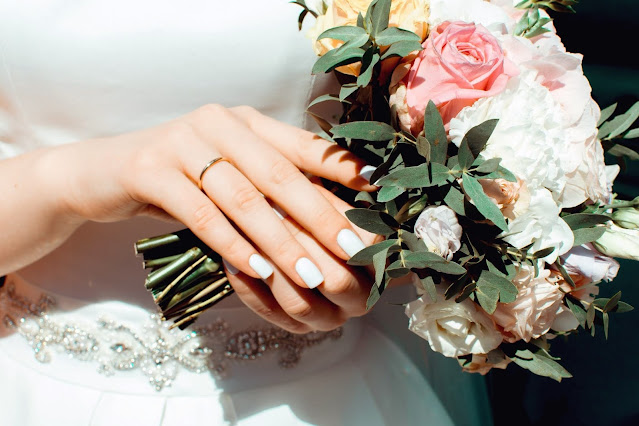Close up of a bride's hand with her wedding ring and bouquet in focus.