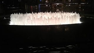 Lincoln Center Fountain at night; a circular fountain with many small upward jets of water