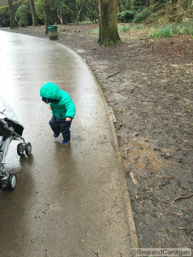 Toddler near muddy puddle looking at feet