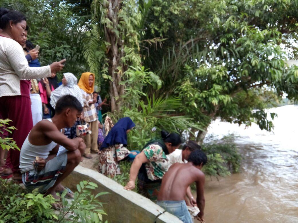 Warga menyaksikan pencari korban yang hanyut di sungai.