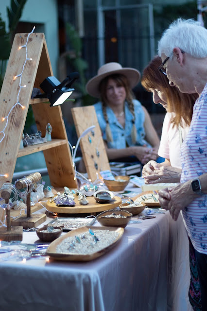 An elderly couple browsing jewelry at an outdoor fair.