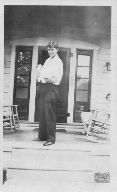 "Front porch of the Ardara, John Urban JR holding infant baby Virginia ""Dolli"""