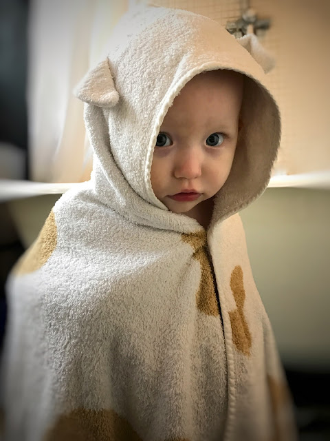 A baby in a bathroom with a roll top bath in the background. The baby is wearing a Cuddledry towel with ears and brown spots