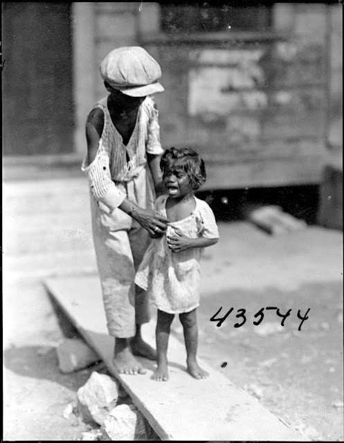 Two young children, one crying. 1922. Guyana, South America