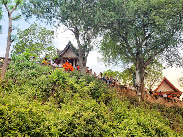 Buddhist monks watch the Luang Prabang boat racing festival from a hilltop temple