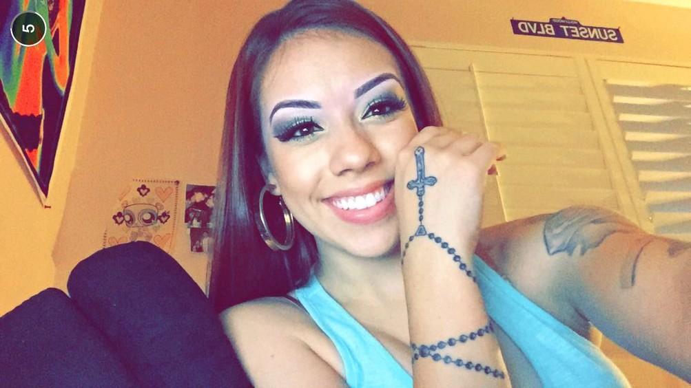 Mujer morena, con tatuaje en la mano de un rosario