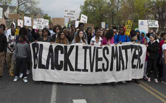 """A group of black and white people protesting Bkack Live Matters with a large banner with an inspription """"Black Lives Matters""""."""