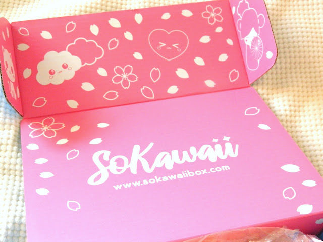 A photo showing a cute pink box interior with cherry blossom flowers, clouds and cat