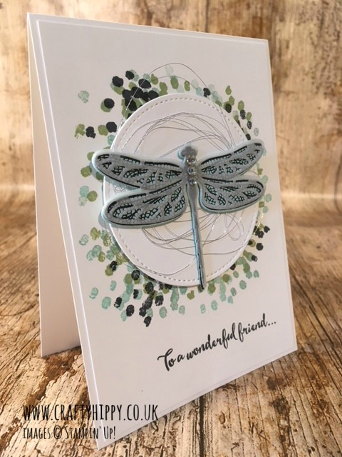 This image is a photograph of a white handmade card showing a dragonfly stamped in Pool Party and Mint Macaron using the Dragonfly Dreams stamp set by Stampin' Up!