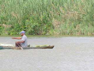 old man paddling a dugout canoe in Belize