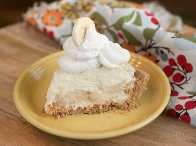 Slice of no cook banana cream pie with a pile of whipped cream on top on a yellow plate