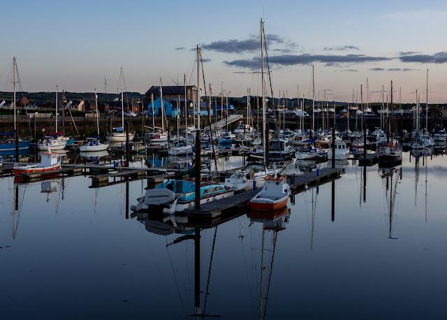 Photo of reflections on the still water at Maryport Marina