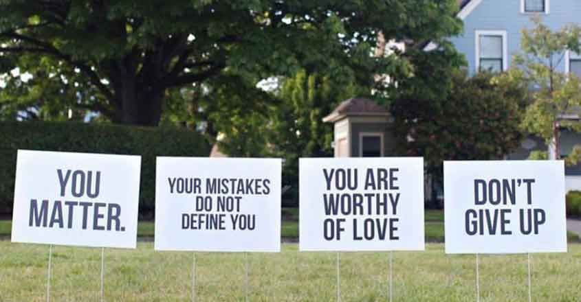 inspirational sign posts on a lawn