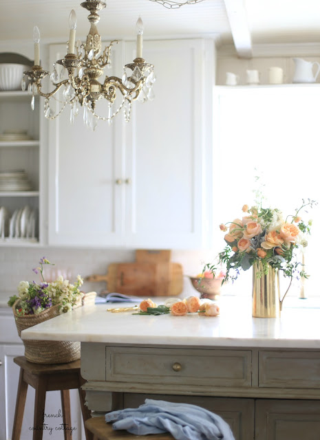 cottage style kitchen with flowers on marble island